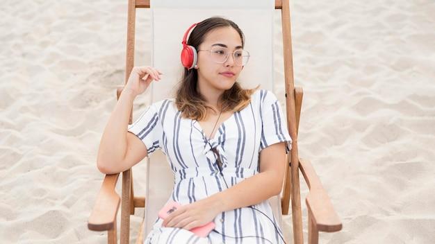 Adolescente bonito relaxante na praia