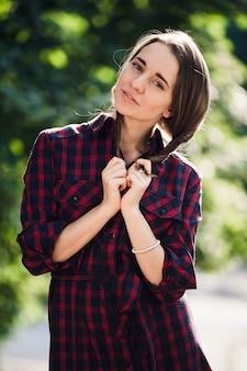 Adolescente bonito vestido casual, brincando com suas tranças, olhando para a câmera e sorrindo, de pé contra a folhagem verde