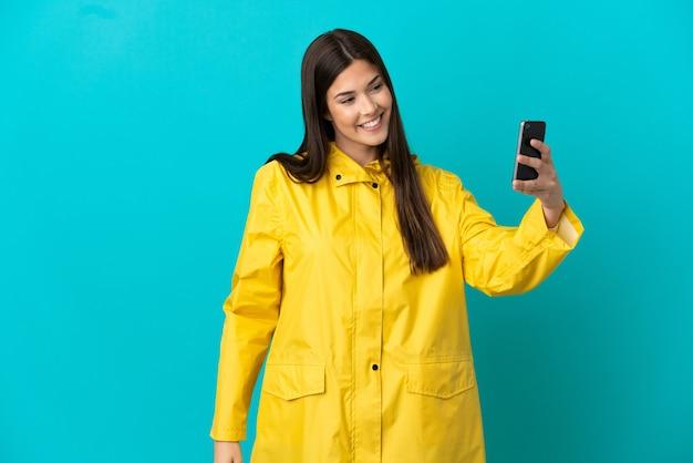 Adolescente brasileira vestindo um casaco à prova de chuva sobre um fundo azul isolado fazendo uma selfie