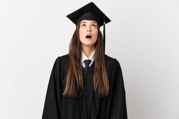 Adolescente brasileiro formado em universidade sobre fundo branco isolado olhando para cima e com expressão de surpresa