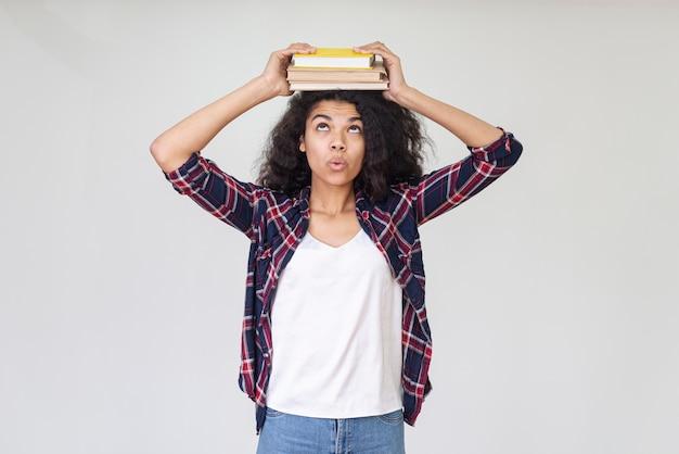 Adolescente brincalhão com livro na cabeça
