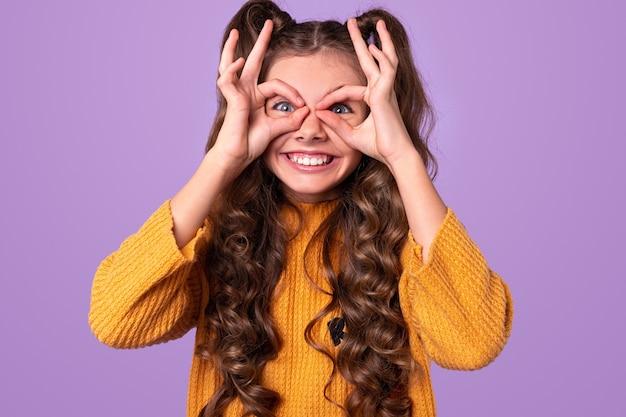 Adolescente brincalhona com rabos de cavalo fazendo gestos de óculos com os dedos