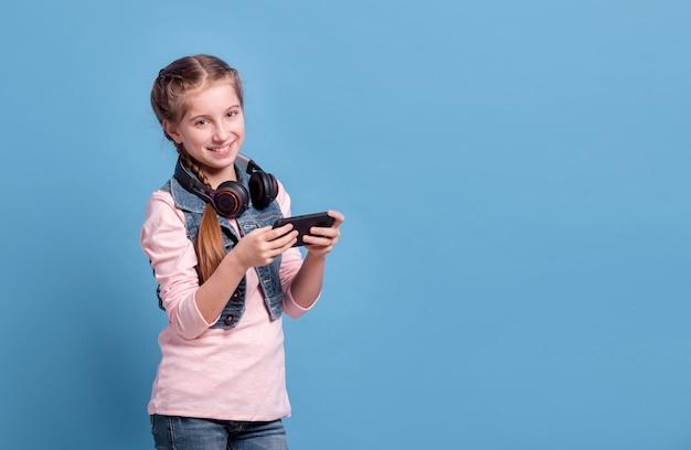 Adolescente brincando com smartphone em fundo azul