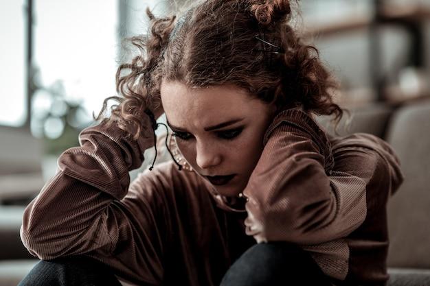 Adolescente cacheada. perto de adolescente encaracolado com maquiagem escura, sentindo-se mal após o divórcio dos pais