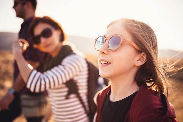 Adolescente, caminhadas em uma estrada de montanha com a família