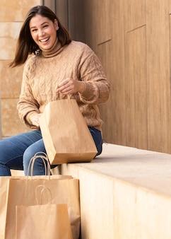 Adolescente casual checando suas sacolas de compras