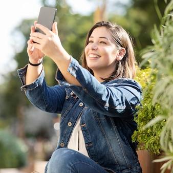Adolescente casual falando uma selfie ao ar livre