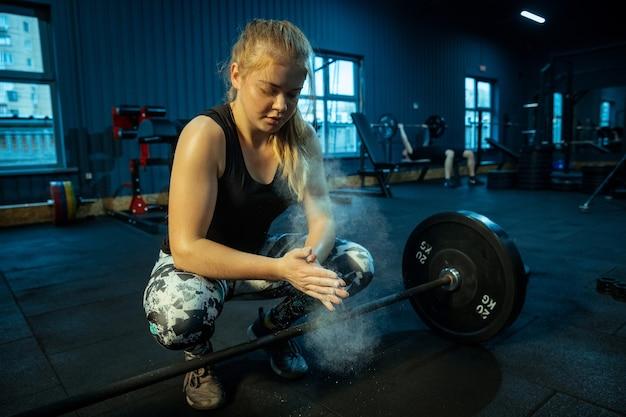 Adolescente caucasiana praticando levantamento de peso no ginásio.