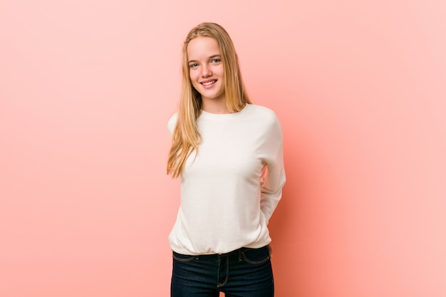Adolescente caucasiano de pé contra um fundo rosa