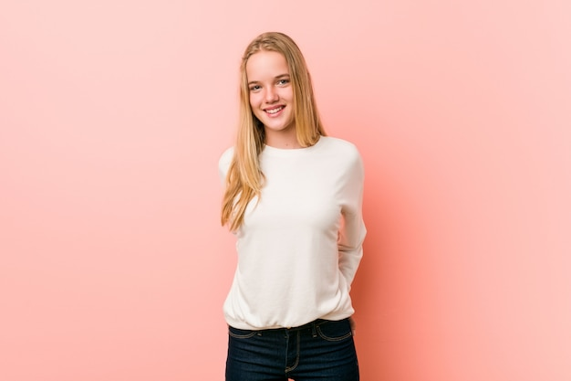 Adolescente caucasiano de pé contra uma parede rosa