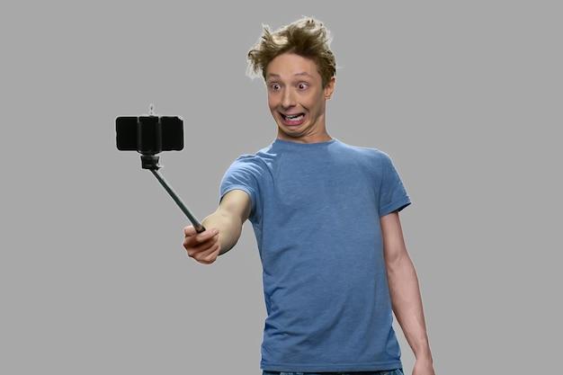 Adolescente caucasiano fazendo selfie. cara engraçado adolescente fazendo careta enquanto posava para a câmera em fundo cinza. juventude, tecnologia e diversão.