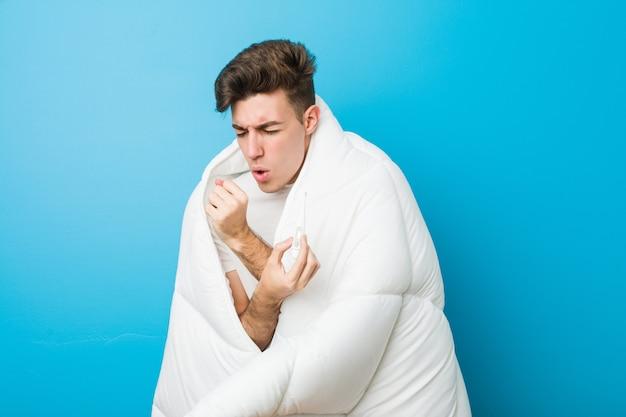 Adolescente caucasiano homem cansado, cobrindo-se com um cobertor e medir sua temperatura corporal