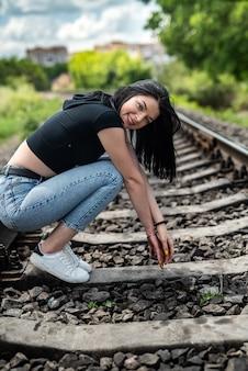 Adolescente caucasiano posando perto da ferrovia, liberdade
