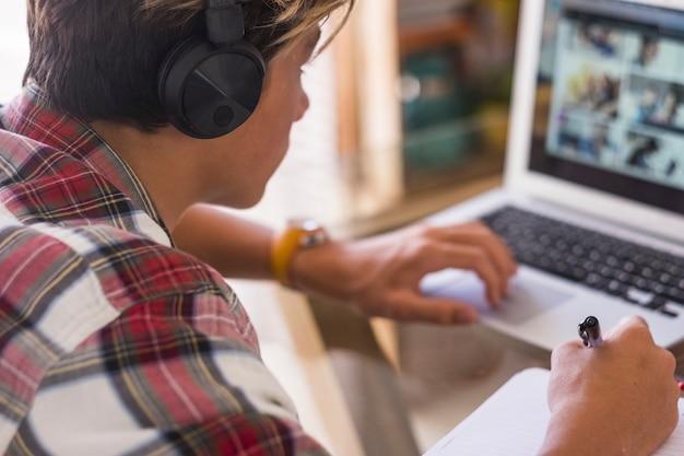 Adolescente caucasiano sozinho se concentra em seus deveres de casa com seu laptop - o cara da geração do milênio trabalha em casa - criança dentro de casa jogando videogame