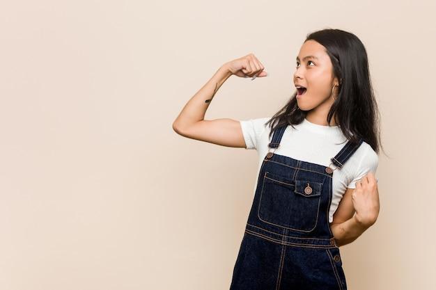 Adolescente chinês bonito novo mulher loura nova que veste um revestimento contra uma parede cor-de-rosa que levanta o punho após uma vitória, conceito do vencedor.