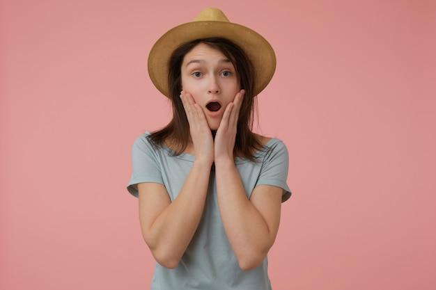 Adolescente, chocada olhando mulher com longos cabelos castanhos. vestindo camiseta e chapéu azulados. tocando suas bochechas, apavorado. isolado sobre parede rosa pastel