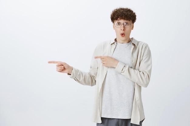 Adolescente chocado e impressionado posando contra a parede branca
