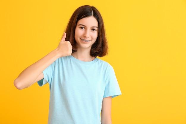 Adolescente com aparelho dentário mostrando gesto do polegar para cima na superfície colorida