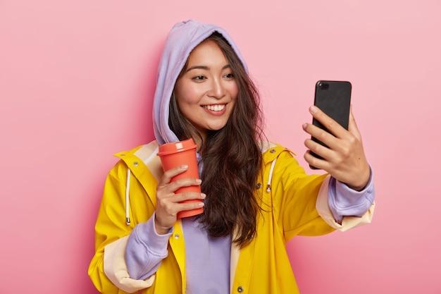 Adolescente com aparência específica tira uma selfie, caminha ao ar livre durante o dia de outono, usa capa de chuva protetora e bebe café no frasco