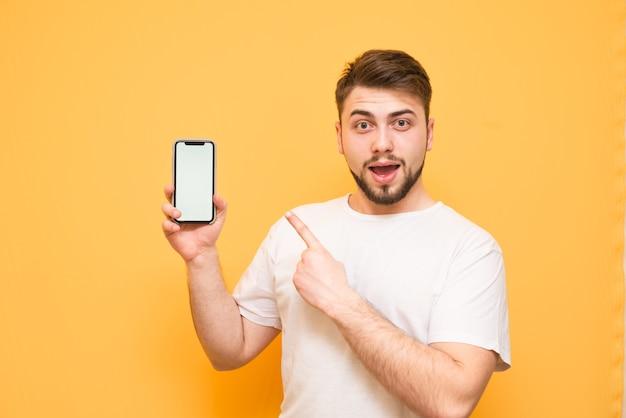 Adolescente com barba, vestindo uma camiseta branca, segurando um smartphone com uma tela branca na mão