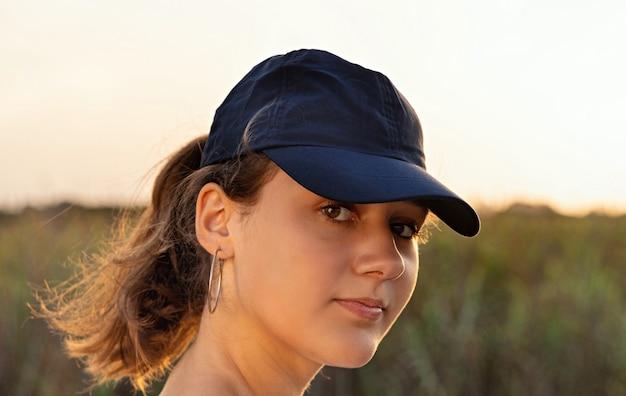 Adolescente com boné de beisebol azul escuro ao pôr do sol, olhando direto para a câmera. maquete de boné