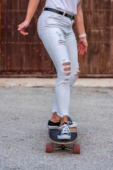 Adolescente com botas marrons praticando longboard andar ao ar livre. vida urbana ativa. subcultura urbana.