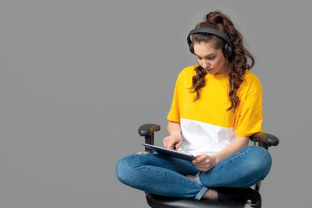 Adolescente com cabelo comprido ondulado, vestido com uma camiseta amarela, sentado em uma cadeira de escritório e usando um tablet, joga, ouve música, isolado na parede cinza