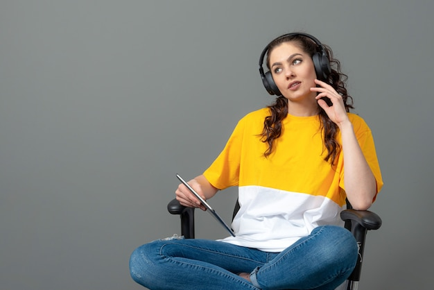 Adolescente com cabelo comprido ondulado, vestido com uma camiseta amarela, sentado em uma cadeira de escritório e usando um tablet, ouve música, isolado na parede cinza