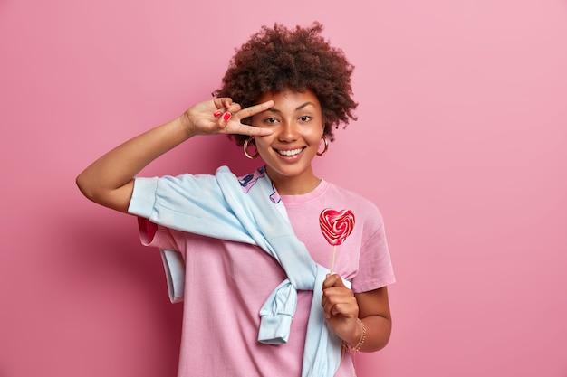Adolescente com cabelo encaracolado faz gesto de vitória sobre o olho, tem uma expressão feliz, segura um pirulito apetitoso no palito, vestida casualmente, posa