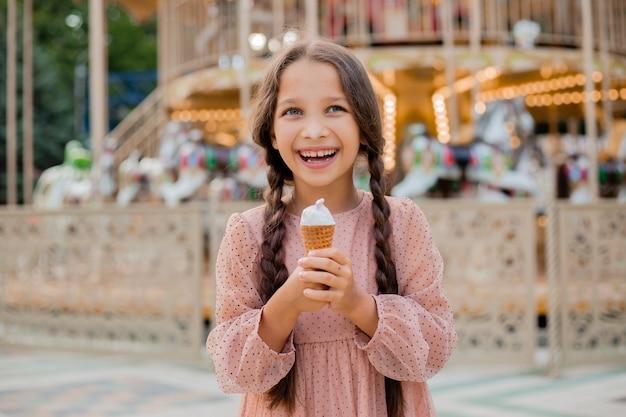 Adolescente com cabelo escuro e rabo de cavalo com sorvete em parque de diversões