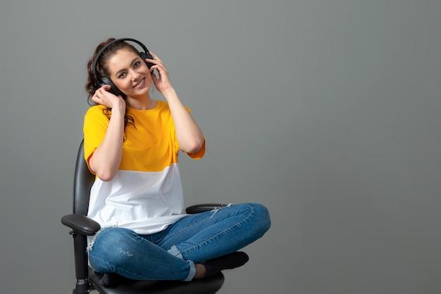 Adolescente com cabelo longo ondulado, vestido com uma camiseta amarela, sentado em uma cadeira de escritório e ouvindo música