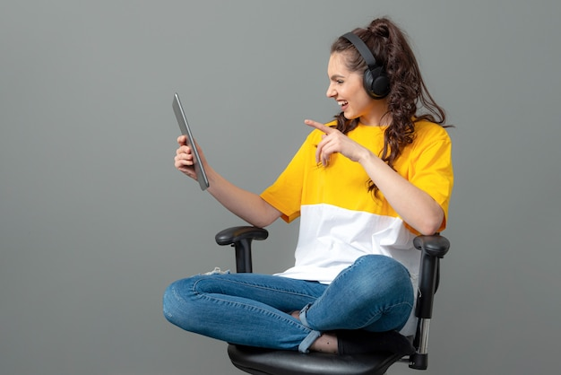 Adolescente com cabelo longo ondulado, vestido com uma camiseta amarela, sentado em uma cadeira de escritório e usando tablet, videochamada, isolado na parede cinza