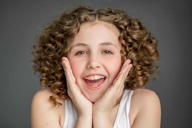 Adolescente com cabelos cacheados ri, emoções de alegria.