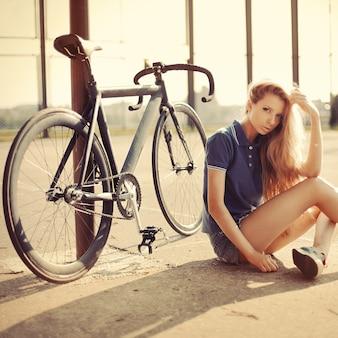 Adolescente com cabelos longos sentado no chão ao pôr do sol