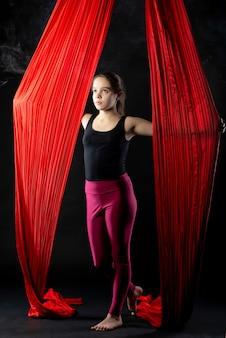 Adolescente com fitas aéreas vermelhas em fundo preto antes do início do show de ginástica
