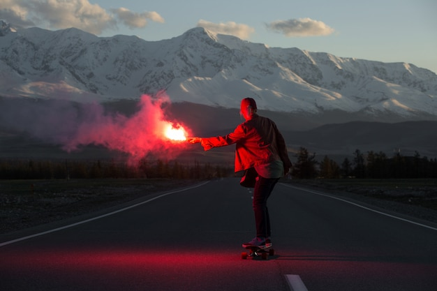 Adolescente com fogo vermelho de skate falsificado na estrada nas montanhas