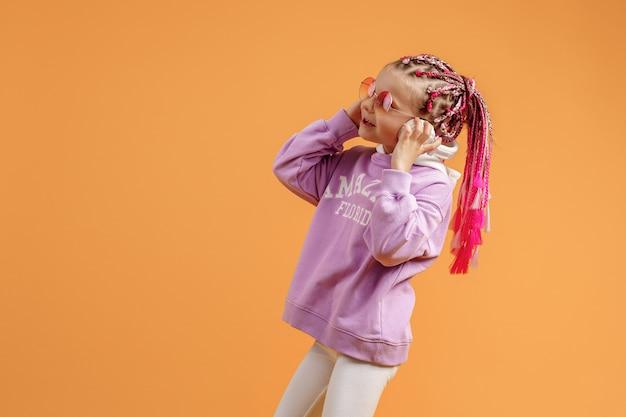 Adolescente com fones de ouvido e dreadlocks brilhantes