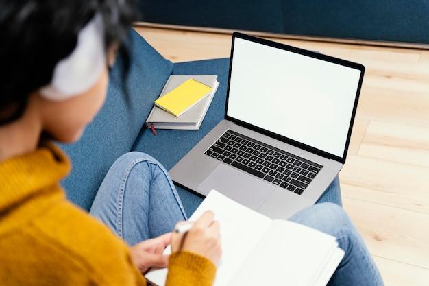 Adolescente com fones de ouvido e laptop durante a escola online