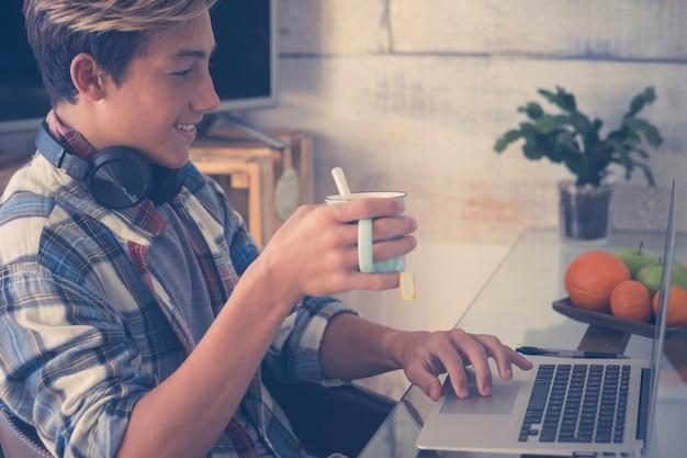 Adolescente com fones de ouvido fazendo lição de casa com laptop e o conceito em casa - interior e estudar - cara olhando e sorrindo