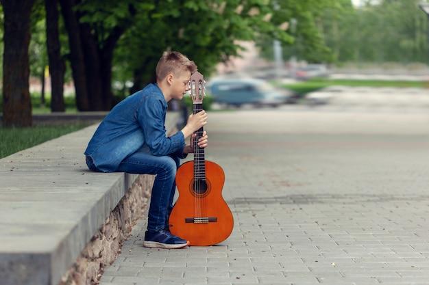 Adolescente com guitarra sentado nos degraus do parque.