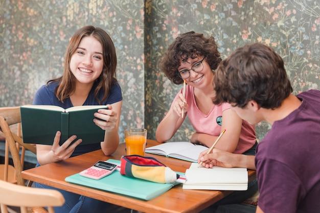Adolescente com livro perto de estudar amigos
