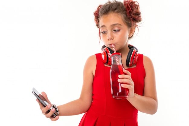 Adolescente com longos cabelos loiros, pontas tingidas de rosa, recheadas em dois tufos, vestido vermelho, com fones de ouvido vermelhos, pulseira, em pé e segurando o telefone na mão e bebe suco na garrafa de vidro com um tubo