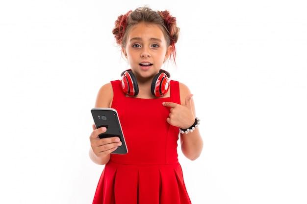 Adolescente com longos cabelos loiros, pontas tingidas de rosa, recheadas em dois tufos, vestido vermelho, com fones de ouvido vermelhos, pulseira, em pé e segurando o telefone na mão