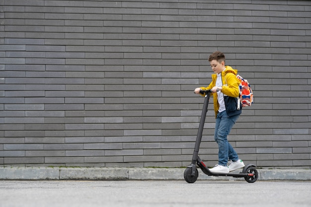 Adolescente com mochila anda de scooter elétrica no fundo da parede de tijolos.