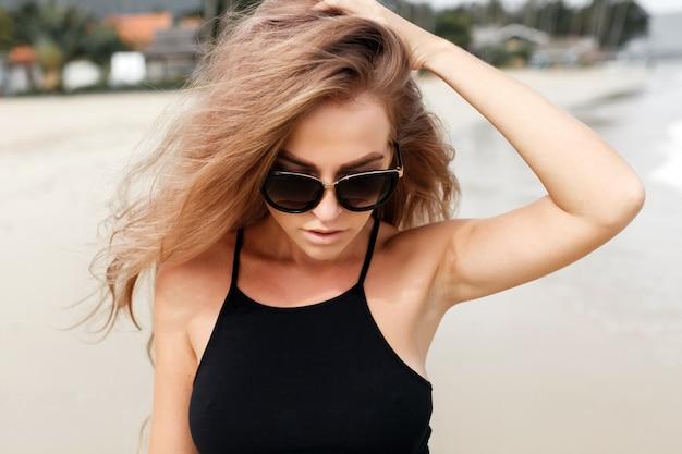 Adolescente com óculos de sol e uma mão em sua cabeça