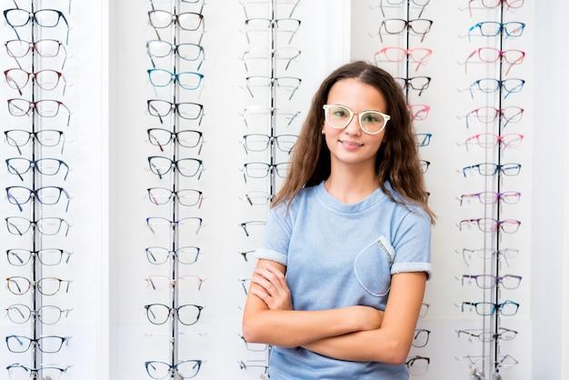 Adolescente com óculos em pé na loja ótica