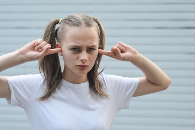 Adolescente com os dedos nos ouvidos