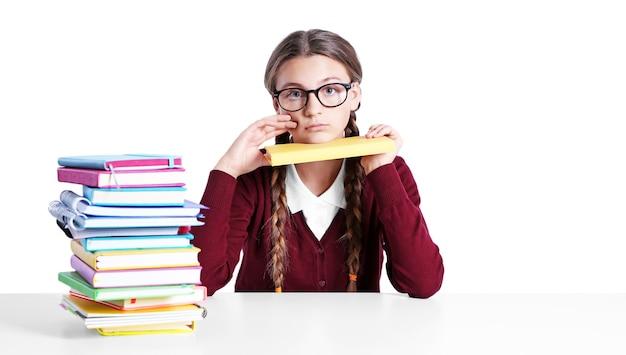 Adolescente com pilha de livros sentada à mesa na superfície branca
