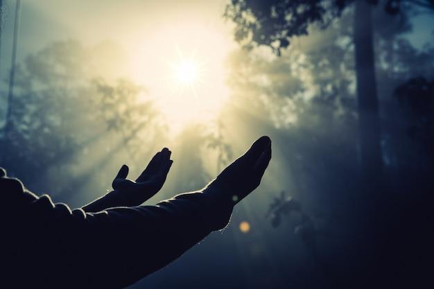 Adolescente com rezar na natureza ensolarada.