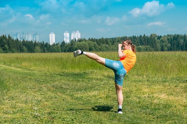 Adolescente com roupas casuais praticando karatê kata ao ar livre apresentando o uro mawashi geri